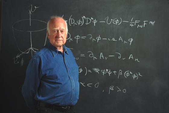 Il Professor Higgs in posa davanti alla lavagna con la sua teoria